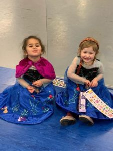 Two girls dressed in Anna dresses sitting on the floor