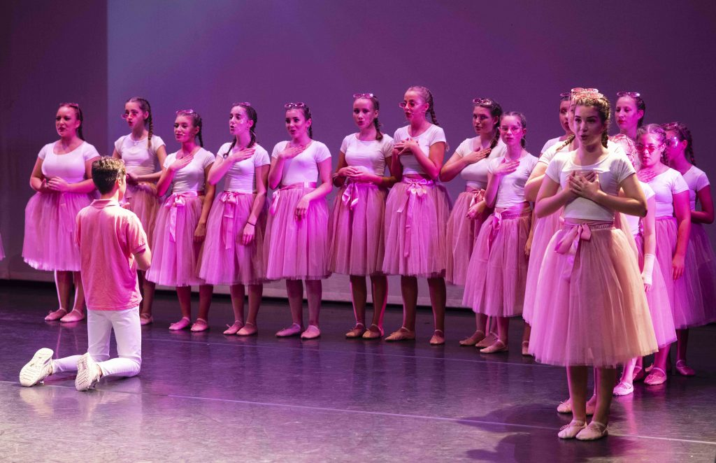 Girls on stage in white tops and pink skirts